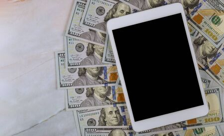 American banknotes hundred dollar bills on digital devices tablet with financial currency e-commerce concept