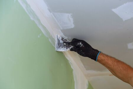 house improvements. putting plaster on the wall with spatula hand holding plastering tool