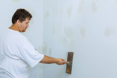 Worker working with putty and spatula work aligns with wall Stockfoto