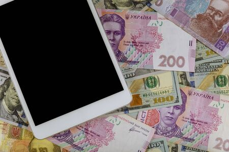 Multi currency money dollars and hryvnia, on digital devices tablet with e-commerce concept finance investment Imagens