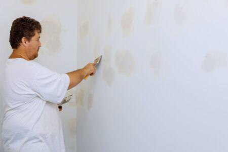 Closeup of a man aligning a wall with spatula and plastering gypsum cardboard wall Stockfoto