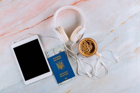 Digital tablet an marble background with cup of black espresso coffee, headphones with International Ukrainian passport travel concept