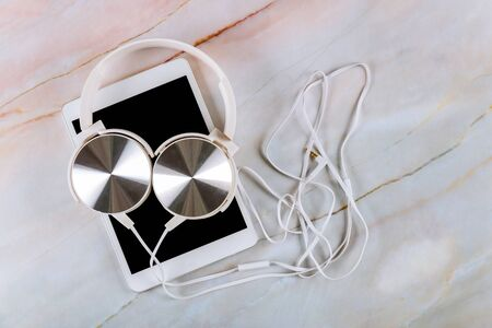 Technology digital tablet on marble background with headphone Imagens