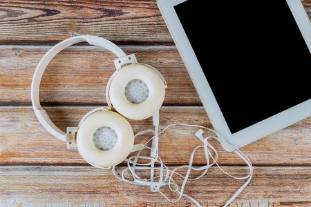 Overhead tablet and headphone in wood background working place, mockup