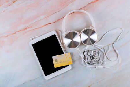 Modern digital tablet and headphones on a marble table credit card and glass of water