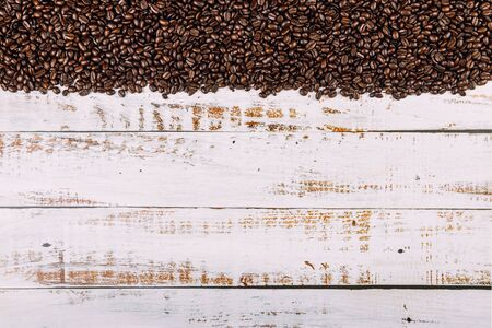 Brown roasted coffee on rustic wood background