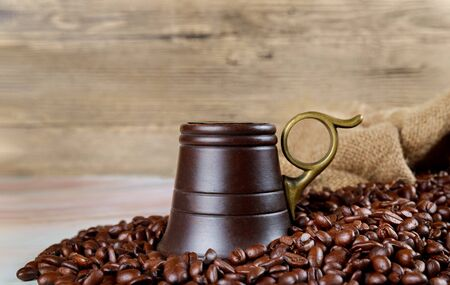 Black coffee beans with wooden cup and bag. Stock Photo