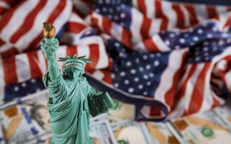 The Statue of Liberty the United States a symbol of freedom and democracy with flag of the United States of America US dollar bills Stock Photo