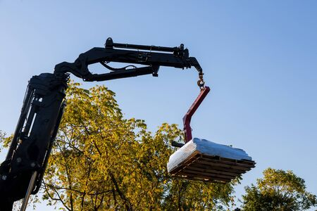 A crane lifting and moving pallet materials to home building roof
