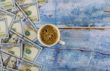 US dollar banknotes american dollars and cup of black espresso coffee on rustic table, top view.