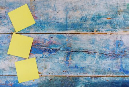 Yellow sticky empty square notes reminder in the blue old wooden background