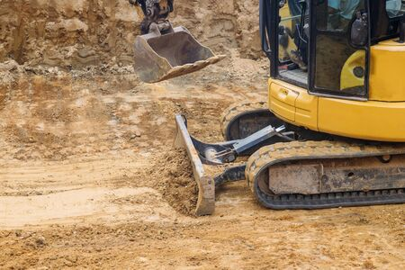 Close up of bulldozer scoop moving earth in preparation for foundation building construction site,