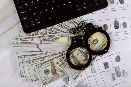 Cyber crime legal law police handcuffs on a hundred dollar bills with computer keyboard technology of criminal taking fingerprint on paper