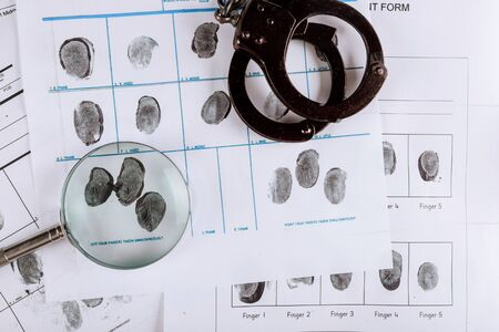 Police handcuffs and criminal fingerprints card, with magnifying glass, top view closeup