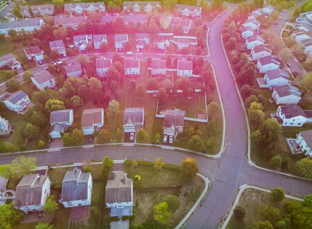 Aerial view over suburban homes and roads aerial view of residential early sunrise