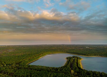 Rainbow in the nice sunset scene over a lake with forest colorful sky 版權商用圖片
