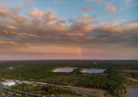 Amazing brilliant rainbow at sunset over lake with forest 版權商用圖片
