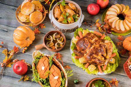 Pavo asado adornado con muchos platos en la mesa de madera. Día de Gracias. Foto de archivo