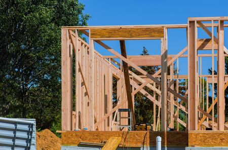 Building with under construction wooden house with timber framing, truss, joist, beam close-up