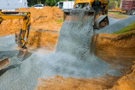 Yellow excavator unloading gravel at construction work equipment machinery for construction of foundation