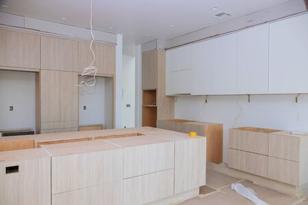 Custom kitchen cabinets in various stages of installation base for kitchen cabinets Foto de archivo