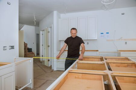 Man using tape measure for measuring on kitchen in furniture for home improvement.