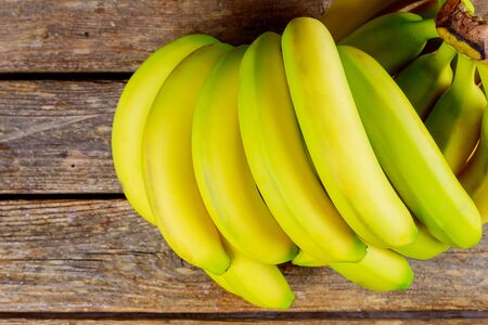 Bunch of ripe bananas on a wooden table. Stock Photo