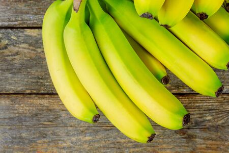 Fresh yellow bananas a bunch on wooden background