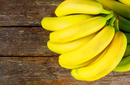 Tropical fruit fresh yellow bananas on wooden table Stock Photo
