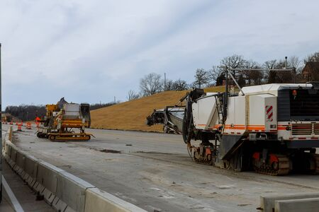 Road construction equipment are working on a new road construction repair route extension