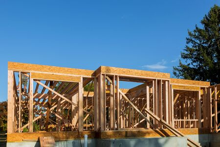 Wood frame work of new residential home under construction under blue sky