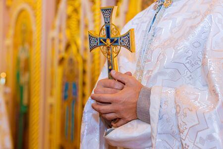 Der heilige orthodoxe Priestervater hält mit einem Kreuz in den Händen