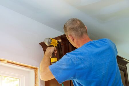 New interior home renovation of modern white kitchen construction worker nailing brad nail air gun to crown moulding on cabinets