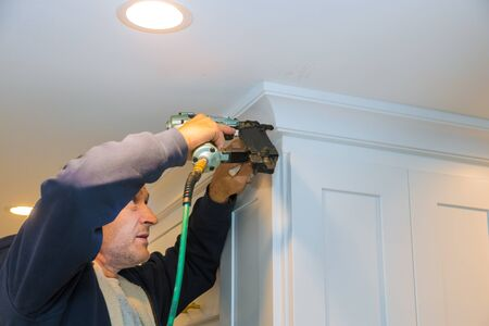 Air nailer tool close up of carpenter using nail gun to crown moldings on kitchen cabinets with white cabinets