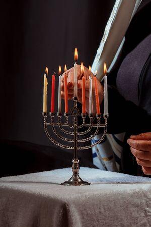 Man hand lighting candles in menorah for hanukka lights candles
