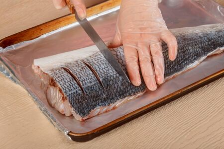 Raw trouts fish in the cuts on fish for baking