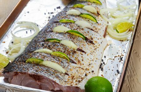 Marinating raw fish for baking on the grill fillet with onions