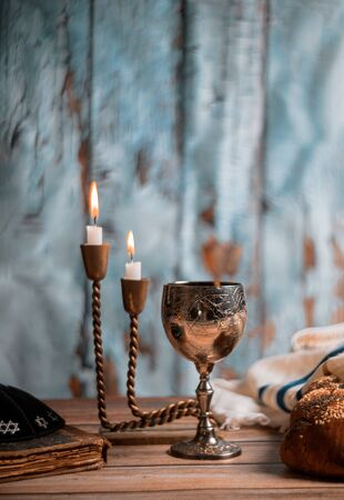 Shabbat Jewish holiday with challah bread on a candles and cup of wine. Stock Photo