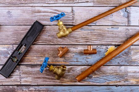 Set of brass plumbing fitting house improvement tools on wooden board