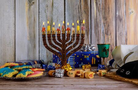 Hanukkah Candles, Jewish Holidays traditional Candelabra , donuts and wooden dreidels spinning top .