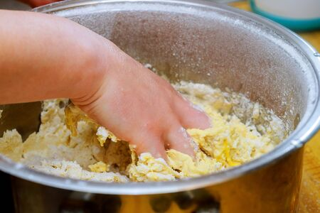 Close-up of woman hands baker kneading with raw yellow dough in a kitchen bowl
