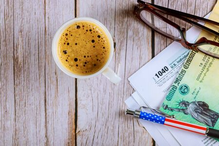 1040 tax forms top view with coffee cup and pencil, refund check with glasses