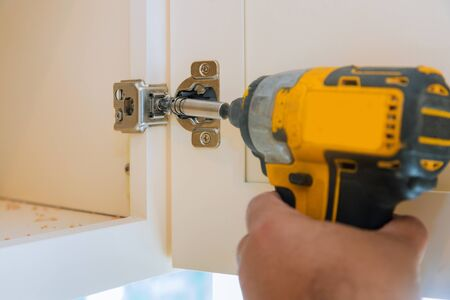 Carpentry assembly of furniture accessories in the kitchen door with a screwdriver a hinge to a kitchen cabinet.