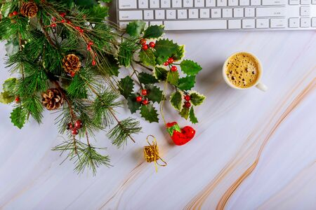 Christmas decoration tree with shiny office table with computer keyboard, cup of coffee, tablet copy space
