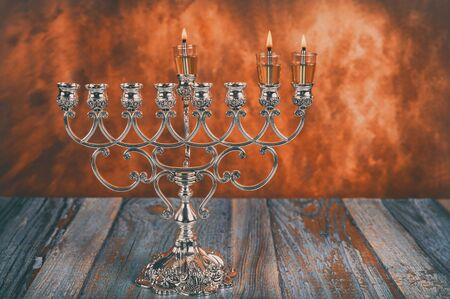 Lights candles on the second day of the Jewish holiday Hanukkah. candles are burning on light of menorah Stock Photo