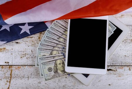 USA economic top view american flag on US dollars on a digital tablet