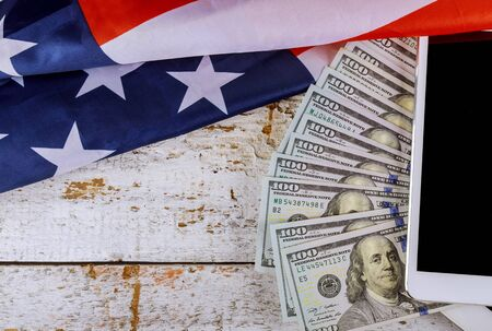 American flag and banknotes 100 USA dollar bill in the USA financial sector on a digital tablet Stock fotó