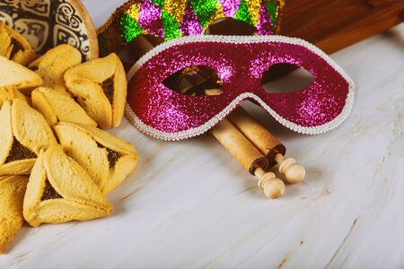 Purim traditional with hamantaschen cookies, noisemaker and carnival mask on old wood background Stock Photo