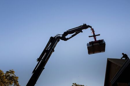 A wooden roof truss being lifted by a boom truck forklift in the roof of a new home Stock Photo