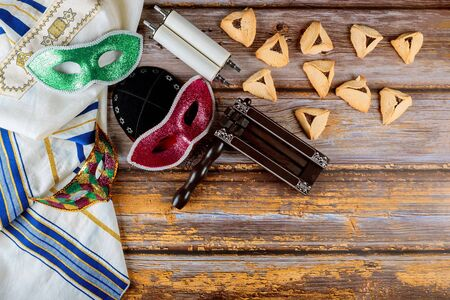 Traditional jewish carnival holiday Purim celebration and cookies hamans ears, noisemaker and mask holy book, talit, kippa